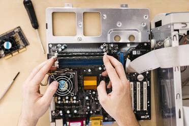 Close-up of technician repairing a desktop computer, changing the computer's RAM - JRFF03547