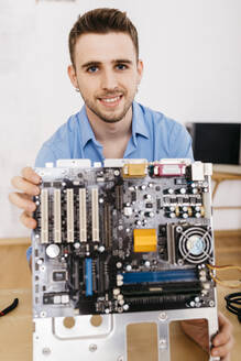 Worker repairing a desktop computer, holding the main board of a computer - JRFF03565
