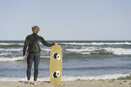 Rear view of kiteboarder standing with his surf board at the beach - AHSF00715