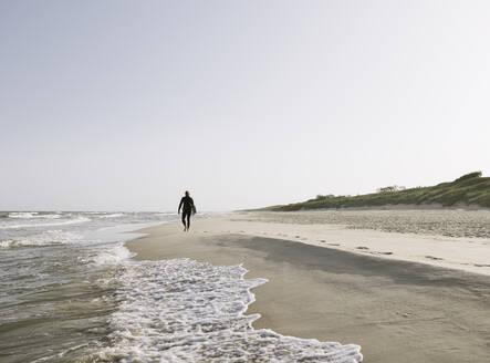 Surfer running at the beach - AHSF00721