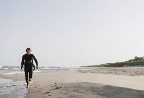 Lithuania, Nida, surfer running in the beach - AHSF00724