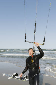 Kiteboarder with his kite at the beach - AHSF00733