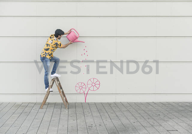 Digital composite of young man watering flower at a wall - UUF18349 - Uwe Umstätter/Westend61
