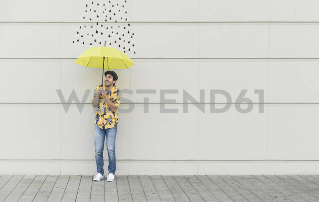 Digital composite of young man holding an umbrella at a wall with raindrops - UUF18361 - Uwe Umstätter/Westend61