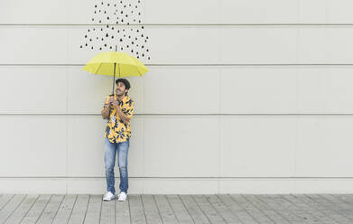 Digital composite of young man holding an umbrella at a wall with raindrops - UUF18361