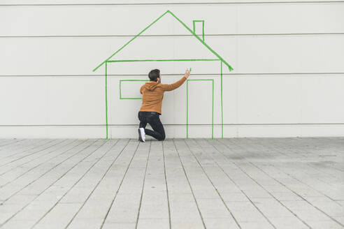Digital composite of young man drawing a house at a wall - UUF18364