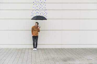 Digital composite of young man holding an umbrella at a wall with raindrops - UUF18370