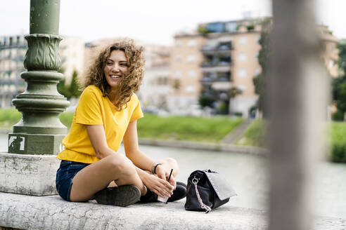 Portrait of happy young woman sitting in the city - GIOF06998