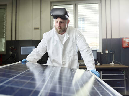 Technician with VR glasses controlling solar panel in lab - CVF01384