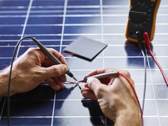 Technician measuring resistor of silicon solar cell - CVF01390