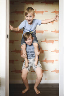 Boy carrying his brother on shoulders at home - EYAF00319