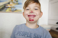 Portrait of grinning boy with blueberry jam in his face - EYAF00334