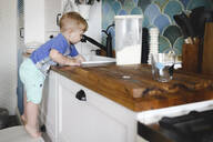 Little boy standing on tiptoes on chair in kitchen washing dishes - EYAF00337