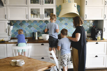 Mother cooking with her three sons in the kitchen - EYAF00343