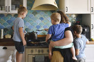 Mother cooking with her three sons in the kitchen - EYAF00346