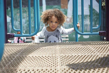Mixed race boy climbing on play structure - BLEF12534