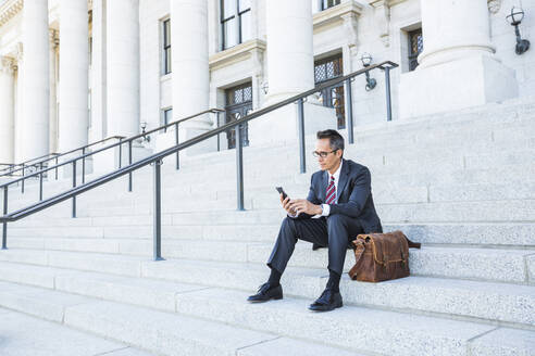Mixed race businessman using cell phone on courthouse steps - BLEF12600