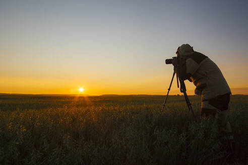 Mixed race man photographing rural sunset - BLEF12657