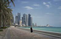 Woman walking on Doha waterfront, Doha, Qatar - BLEF12723