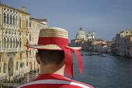Caucasian gondolier admiring Venice cityscape, Veneto, Italy - BLEF12750