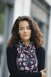 Mixed race woman standing in city - BLEF12783