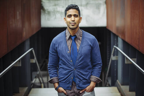 Indian businessman standing on office steps - BLEF12792