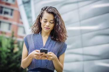 Mixed race businesswoman using cell phone outdoors - BLEF12801