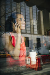 Mixed race woman talking on cell phone in cafe - BLEF12810