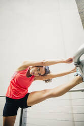 Mixed race athlete stretching on banister - BLEF12828