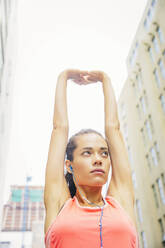 Mixed race athlete stretching in city - BLEF12834