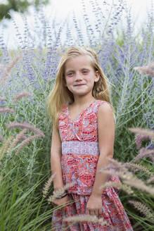Caucasian girl smiling in tall grass - BLEF12915