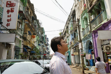 Asian businessman standing in city - BLEF12942