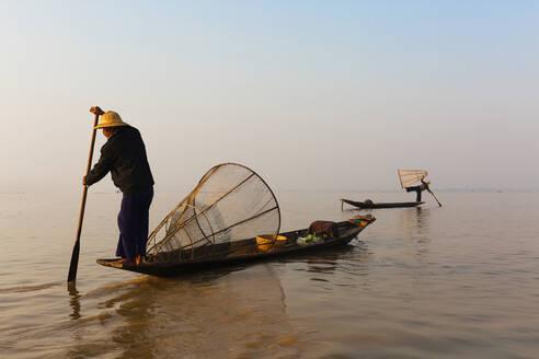 Asian fisherman rowing canoe on still lake - BLEF12948