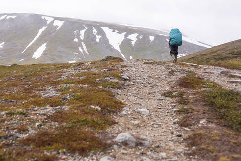 Mari backpacker walking on mountain path - BLEF12963