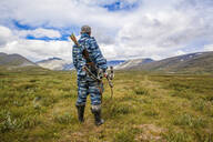 Mari hunter carrying crossbow in remote field - BLEF12975