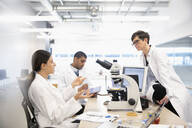 Scientists working at microscope in laboratory - HEROF37326