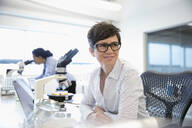 Smiling, confident female scientist working at microscope in laboratory - HEROF37338