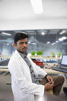 Portrait confident male engineer working at laptop in laboratory - HEROF37362
