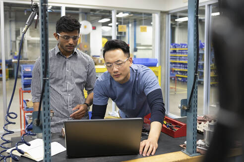 Male engineers working at laptop in research lab - HEROF37377