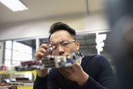 Focused male engineer assembling circuit board in research lab - HEROF37389