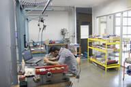 Focused male engineer assembling circuit board in research lab - HEROF37392