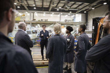Female supervisor talking with machinists in factory - HEROF37464