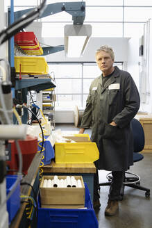 Portrait confident male machinist at workbench in factory - HEROF37503