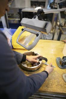 Male machinist assembling equipment under magnifying lamp - HEROF37524