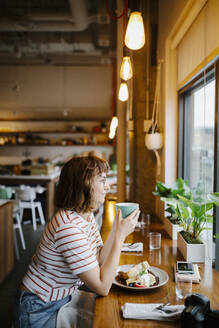 Confident young woman dining at counter in restaurant - HEROF37602