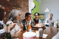 Business people watching colleague blow out birthday cake candles in office - HEROF37812