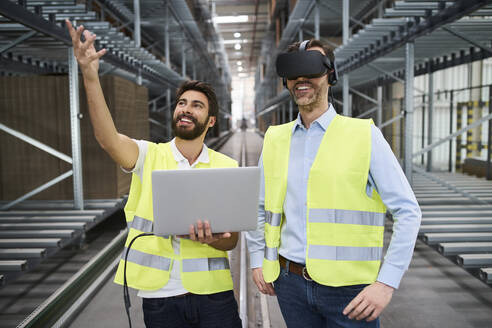 Man with laptop and businessman wearing VR glasses in factory - BSZF01183