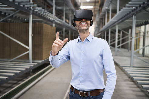 Businessman wearing VR glasses in factory - BSZF01186