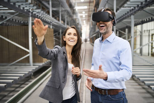 Happy businesswoman and businessman wearing VR glasses in factory - BSZF01189