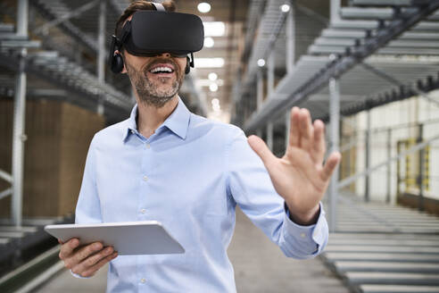 Businessman with tablet wearing VR glasses in factory - BSZF01192